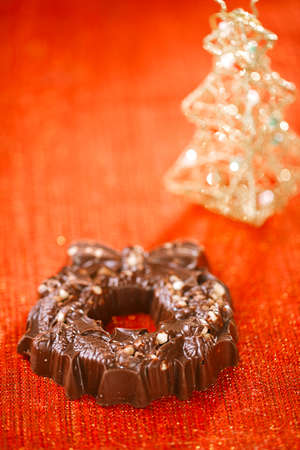 festive christmas wreath - dark chocolate with nuts and rice crisps on red golden  photo