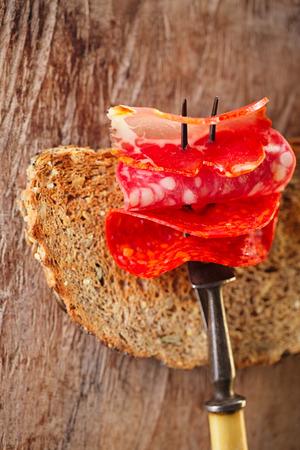 salame: lomo pork loin,  chorizo pamplona, salchichon salame on meat fork and bread