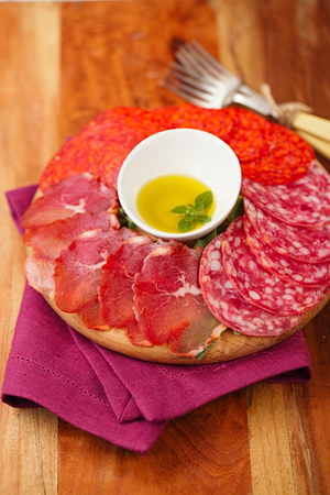 wooden board of Assorted Cured Meats, olive oil, fork and glasses of white wine on vintage stool photo