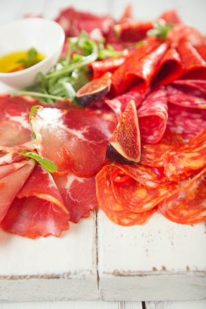cold cuts: antipasti Platter of Cured Meat,   jamon, sausage, salame  on textured white wooden table