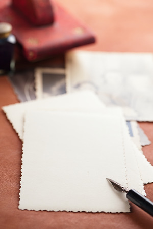 blotter: vintage red leather ink blotter  with retro post cards on leather table, shallow dof Stock Photo