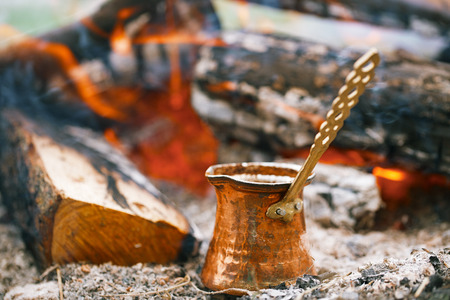cezve: Making coffee in the fireplace  on camping or hiking in the nature Stock Photo