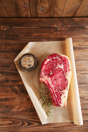 lb: raw beef Rib bone  steak  on paper  and table with 2lb iron weight