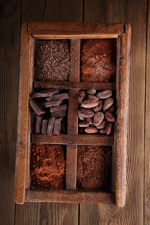 cocoa beans: old spicy box full of chocolate - cocoa and sugar, cocoa beans, grated chocolate, hot chocolate flakes, solid pieces, dark cocoa powder Stock Photo