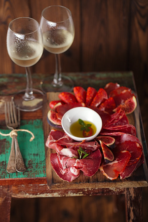 Cured Meat and vintage forks on textured Chalkboard and old wooden stool background photo