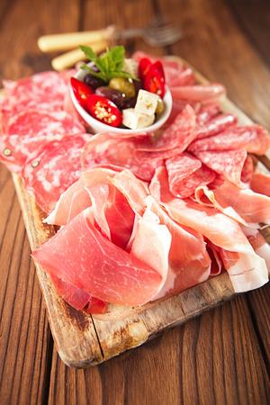 antipasti: antipasti Platter of Cured Meat on textured wooden table Stock Photo