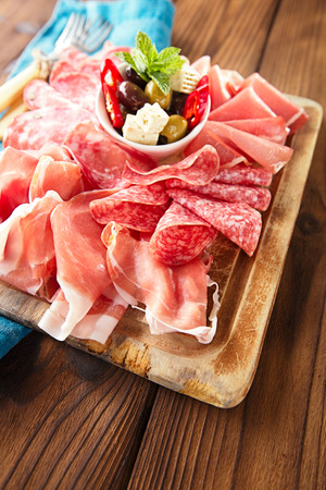 cold cuts: antipasti Platter of Cured Meat,   jamon, olives, sausage, salami,  ciabatta and white wine glasses on textured wooden table Stock Photo