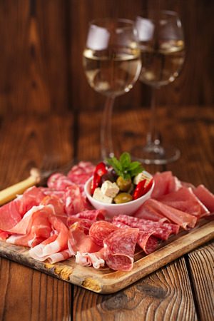 antipasto: antipasti Platter of Cured Meat,   jamon, olives, sausage, salami,  ciabatta and white wine glasses on textured wooden table Stock Photo