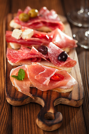 Cured Meat and ciabatta bread on wooden board, white wine on background photo
