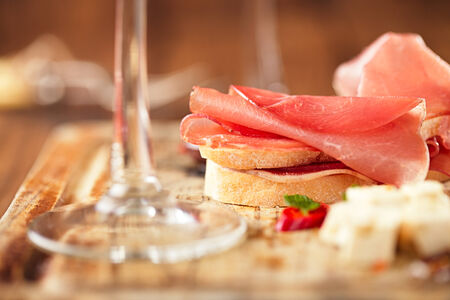 cold cuts: Cured Meat and ciabatta bread on wooden board, white wine on background