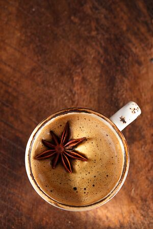 spiced: A cup of spiced coffee with anis star and cinamon sticks and sugar