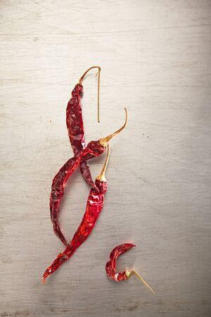 chiles secos: secos chiliies enteros rojos en vieja lata de metal con textura Foto de archivo