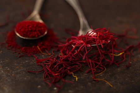 moroccan cuisine: saffron spice threads and powder  in vintage  old spoons,  old metal background, closeup Stock Photo