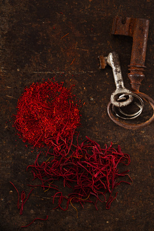 grinded: saffron spice in pile threads and powder on old metal background, closeup Stock Photo