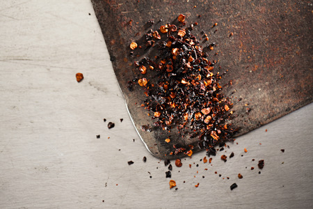 chili powder: chipotle - jalapeno smoked chili flakes,   and whole in iron weight bowl on old textured metal Stock Photo