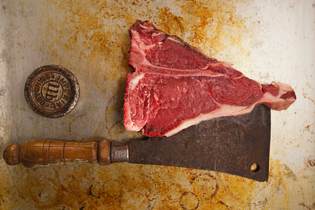 beef steak t-bone with vintage butcher cleaver knife photo