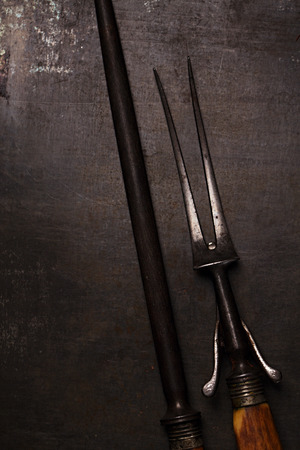stylish vintage meat fork and sharpener on metal backdrop, dark light photo