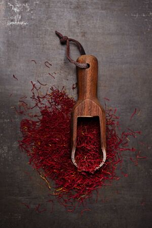 grinded: saffron spice threads   in vintage  old scoop,  old metal background, closeup