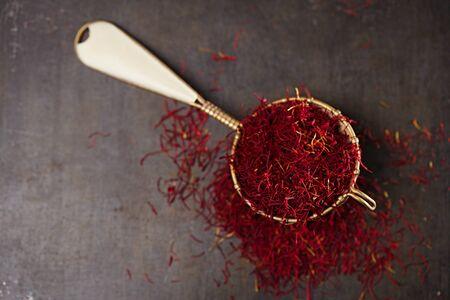 saffron spice threads and powder  in vintage  old sieve,  old metal background, closeup photo