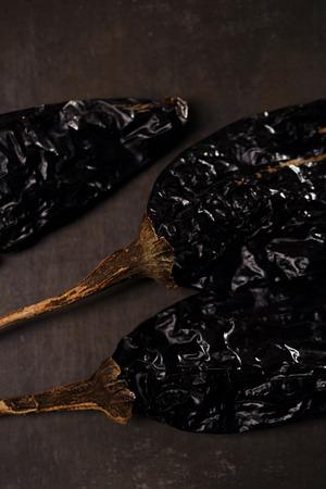 chiles secos: chipotle - jalapeño ahumado chile entero en el fondo de metal Foto de archivo