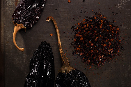 pepper flakes: chipotle - jalapeno smoked chili flakes and whole on metal background