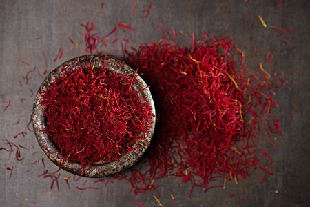 grinded: saffron spice threads and powder  in vintage iron dish  old metal background, closeup