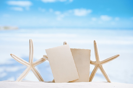 white starfish with blank retro photo on white sand beach, sky and seascape, shallow dof photo