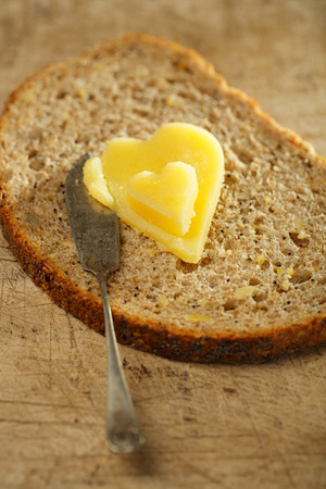 ghee: ghee or melted butter in heart shape on wholemeal bread Stock Photo