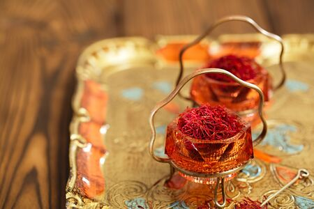 moroccan cuisine: saffron spice in antique vintage glass bowl, closeup Stock Photo