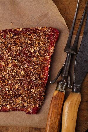 roughly: spice rubbed raw  beef, making jerky meat on woodeb backdrop with vintage curving fork and knife