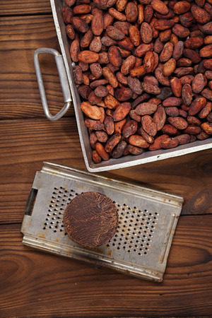 roasting pan: roasted cocoa beans in Vintage heavy cast aluminum roasting pan and and 100% solid chocolate on wood background