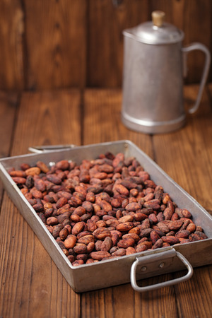 roasting pan: roasted cocoa chocolate beans in Vintage heavy cast aluminum roasting pan on wood background