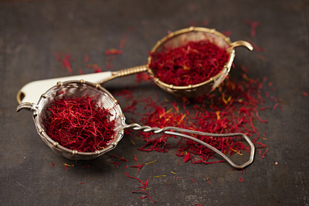 grinded: saffron spice threads and powder  in vintage  old sieve,  old metal background, closeup Stock Photo