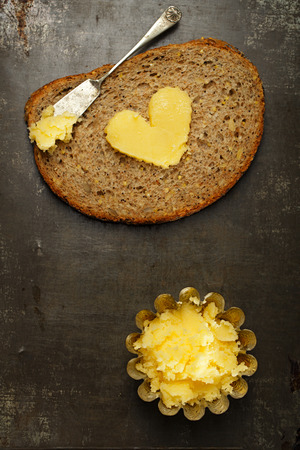 clarified: ghee or melted butter in heart shape on wholemeal bread Stock Photo