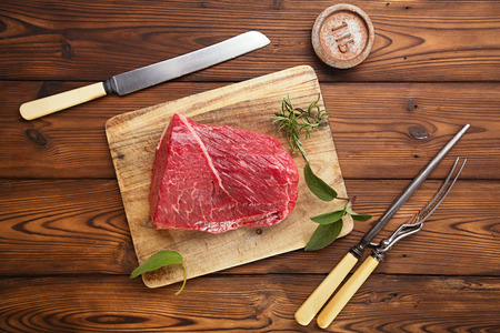 raw beef meat fillet  on wooden  table with meat fork and 1lb iron weight Stock Photo