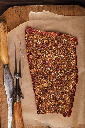 roughly: spice rubbed raw  beef fillet, making jerky meat on woodeb backdrop with vintage curving fork and knife