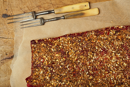 roughly: spice rubbed raw  beef, making jerky meat on wooden backdrop with vintage curving fork
