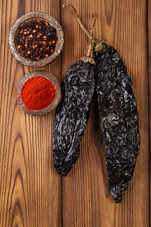 pepper flakes: chipotle - jalapeno smoked chili flakes, milled  and whole in iron weight bowl on old textured wood