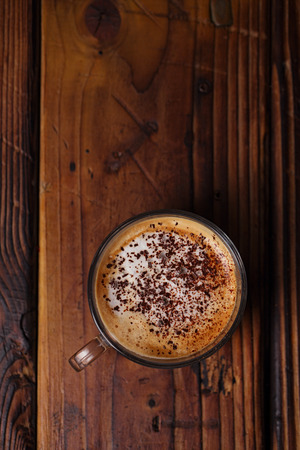 glass coffee cup on rustic textured wooden table with dark light