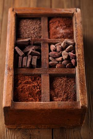 frijoles: vieja caja picante llena de chocolate - cacao y azúcar, granos de cacao, chocolate rallado, copos de chocolate caliente, piezas sólidas, polvo de cacao oscuro