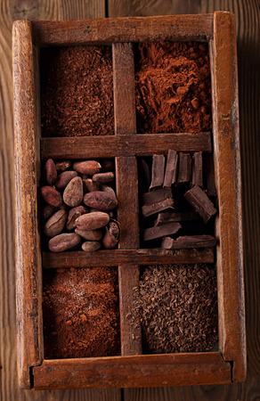 cocoa powder: old spicy box full of chocolate - cocoa and sugar, cocoa beans, grated chocolate, hot chocolate flakes, solid pieces, dark cocoa powder Stock Photo