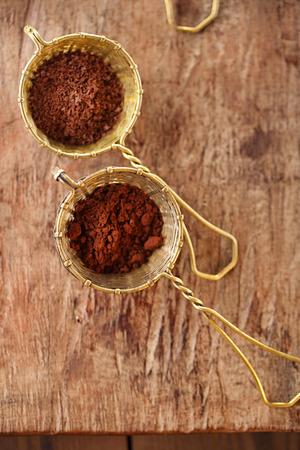 frijoles: cacao en polvo en viejos tamices de plata de estilo rústico sobre fondo de madera vieja