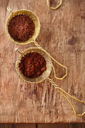 cocoa bean: cocoa powder  in old rustic style silver sieves on old wooden background Stock Photo