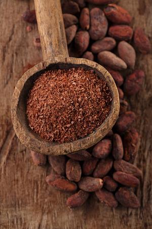 frijoles: chocolate negro rallado en cuchara de madera vieja en el cacao tostado granos de chocolate de fondo
