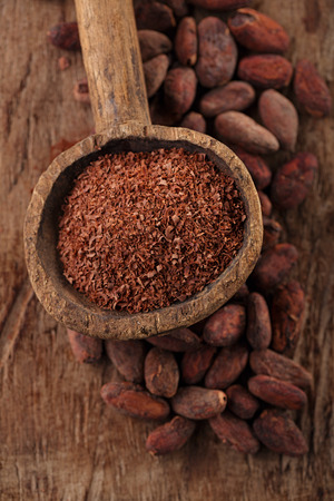cocoa bean: grated dark chocolate in old wooden spoon on roasted cocoa chocolate beans background