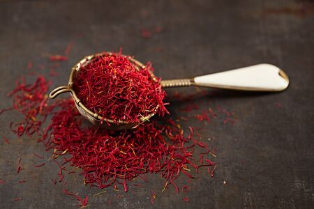 saffron spice threads and powder  in vintage  old sieve,  old metal background, closeup Stockfoto