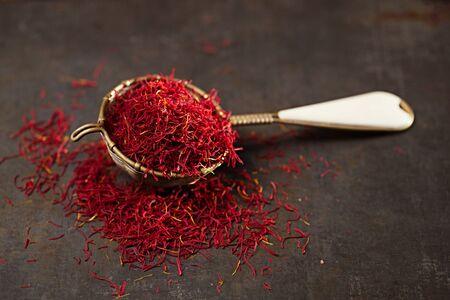 sieve: saffron spice threads and powder  in vintage  old sieve,  old metal background, closeup Stock Photo