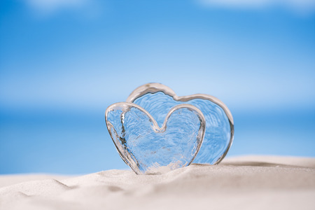 love hearts: clear glass hearts on white sand beach, ocean,  sky and seascape