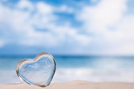 clear sky: clear glass heart on white sand beach, ocean,  sky and seascape
