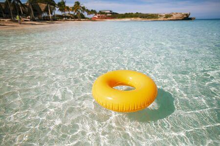 schwimmring: Schwimmring auf klare Meer mit Strand, flache DOF Lizenzfreie Bilder